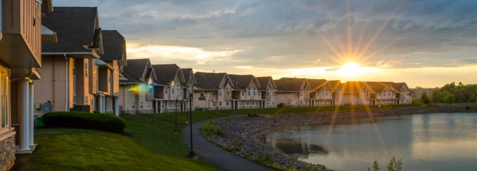Sun setting behind a row of apartment buildings on a lake