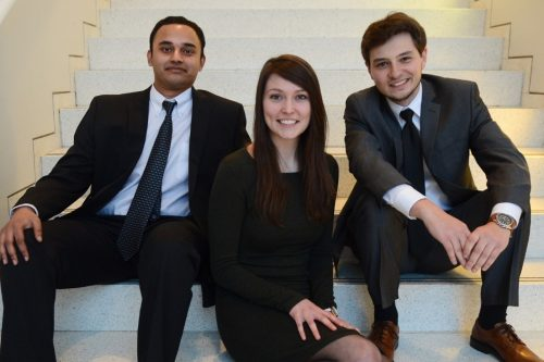 Thiru Vikram, Emilie Reynolds, and Alexander Zhitelzeyf sitting on stairs