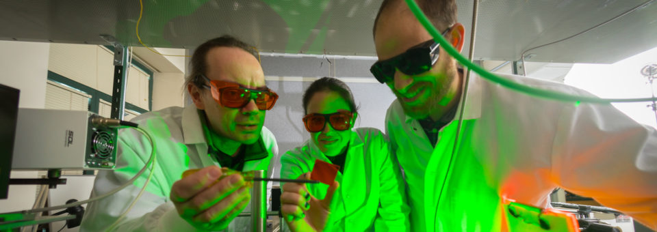 Three researchers looking at a sample in a chemistry lab